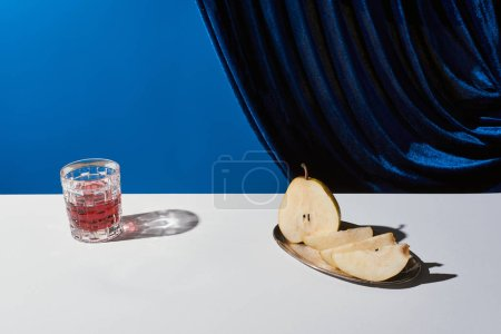 klasyczna martwa natura z gruszką, szklanka z napojem na białym stole w pobliżu welurowej zasłony odizolowanej na niebiesko