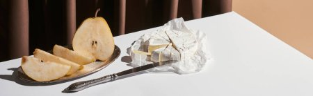 Photo for Classic still life with pear, brie cheese and knife on table near curtain isolated on beige, panoramic shot - Royalty Free Image