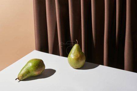 Photo pour Nature morte classique avec poires sur table près d'un rideau isolé sur beige - image libre de droit
