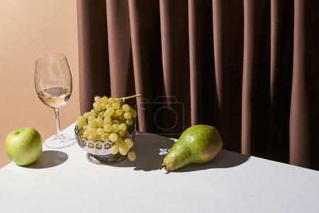 Foto de La vida clásica con vino blanco y frutas sobre la mesa cerca de la cortina aislada sobre la colza. - Imagen libre de derechos
