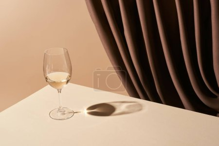 Photo for Classic still life with glass of white wine on table near curtain isolated on beige - Royalty Free Image