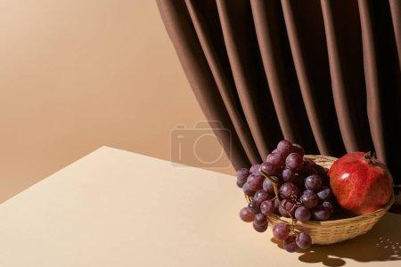 Foto de La vida aún clásica con granado y uva en cesta de mimbre en la mesa cerca de cortina aislada en beige. - Imagen libre de derechos