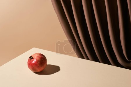 Foto de La vida clásica con granado en la mesa cerca de la cortina aislada sobre la colza. - Imagen libre de derechos