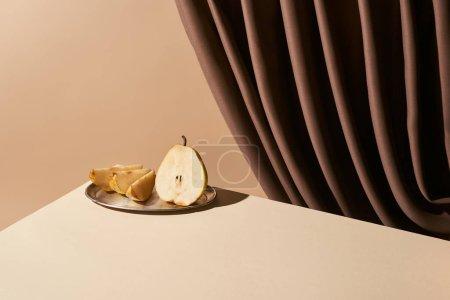 Foto de La vida aún clásica con pera en la placa de plata en la mesa cerca de cortina aislada en beige. - Imagen libre de derechos
