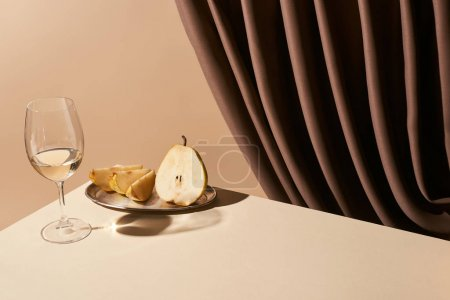 Foto de La vida clásica con pera y vino blanco sobre la mesa cerca de la cortina aislada en beige. - Imagen libre de derechos