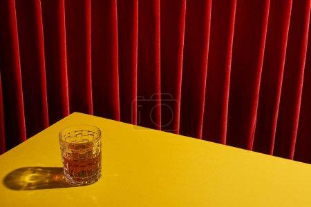 Foto de La vida clásica con vidrio de bebida en la mesa amarilla cerca de la cortina roja - Imagen libre de derechos