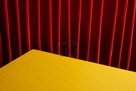Foto de Fondo con mesa amarilla cerca de la cortina roja - Imagen libre de derechos