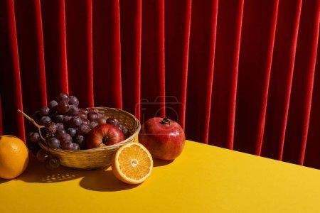 Foto de La vida clásica con frutos en cesta de mimbre en la mesa amarilla cerca de la cortina roja. - Imagen libre de derechos