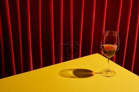 classic still life with glass of red wine on yellow table near red curtain