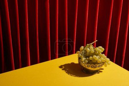 Foto de La vida clásica con uva verde en la mesa amarilla cerca de la cortina roja - Imagen libre de derechos