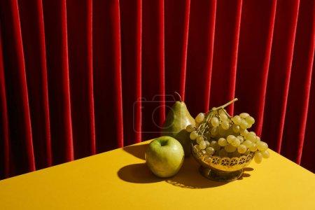 Foto de La vida clásica con frutos verdes en la mesa amarilla cerca de la cortina roja - Imagen libre de derechos