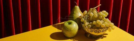 Foto de La vida clásica con frutos verdes en la mesa amarilla cerca de la cortina roja, tiro panorámico. - Imagen libre de derechos