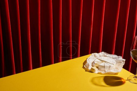 classic still life with Camembert near glass of red wine on yellow table near red curtain