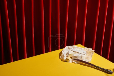 Photo for Classic still life with Camembert near knife on yellow table near red curtain - Royalty Free Image