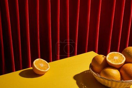 Foto de La vida clásica con naranjas en cesta de mimbre en la mesa amarilla cerca de la cortina roja. - Imagen libre de derechos