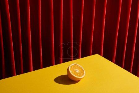 Foto de La vida clásica con la mitad naranja en la mesa amarilla cerca de la cortina roja - Imagen libre de derechos