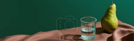Photo pour Nature morte classique avec poire et eau en verre sur la table avec nappe brune isolée sur vert, plan panoramique - image libre de droit
