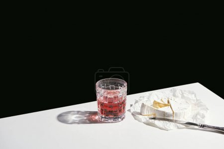 Photo for Classic still life with Camembert cheese and red wine in glass on white table isolated on black - Royalty Free Image