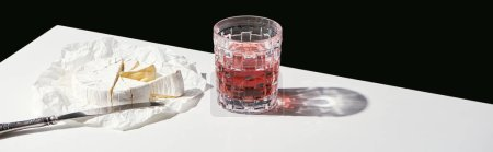 Photo for Classic still life with Camembert cheese and red wine in glass on white table isolated on black, panoramic shot - Royalty Free Image