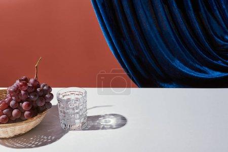 klasyczna martwa natura z winogronami, szkło na białym stole w pobliżu welurowej zasłony odizolowanej na brązie