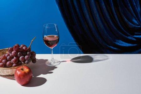 Foto de La vida clásica con frutas, el vino tinto en la mesa blanca cerca de la cortina de terciopelo aislado en azul. - Imagen libre de derechos