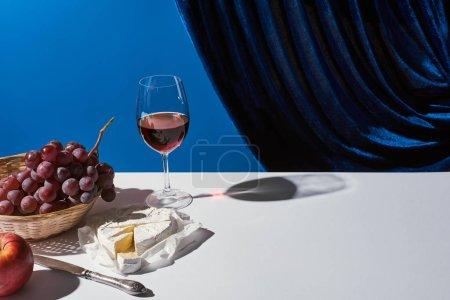 Photo pour Nature morte classique avec fruits, vin rouge et fromage Camembert sur table blanche près du rideau de velours isolé sur bleu - image libre de droit