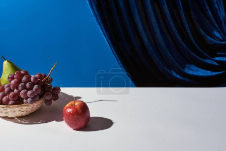 Photo for Classic still life with grape, pear and apple in wicker basket on white table near velour curtain isolated on blue - Royalty Free Image