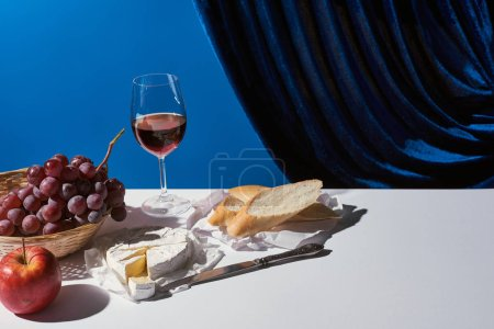 Photo for Classic still life with fruits, red wine, baguette and Camembert cheese on white table near velour curtain isolated on blue - Royalty Free Image