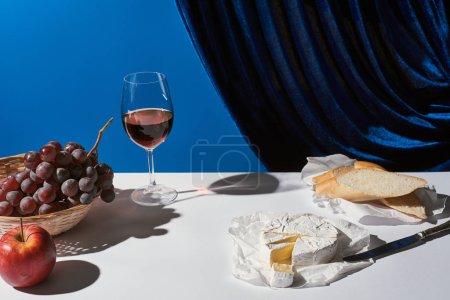 Foto de La vida clásica con frutas, vino tinto, baguette y queso Camembert en la mesa blanca cerca de la cortina de terciopelo aislado en azul. - Imagen libre de derechos
