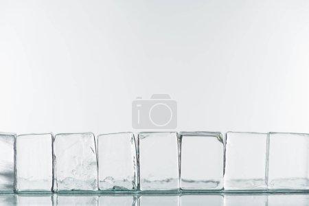 Foto de Corte transparente de hielo cuadrado en línea aislada sobre blanco - Imagen libre de derechos