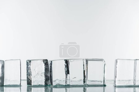 Photo for Transparent clear square ice cubes in line isolated on white - Royalty Free Image