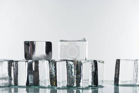 Photo pour Faire fondre des glaçons carrés transparents et clairs isolés sur du blanc - image libre de droit