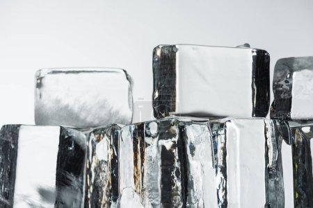Foto de Cerca de la vista de fundir cubos transparentes de hielo cuadrado aislados sobre blanco. - Imagen libre de derechos