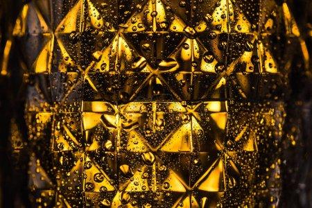 Photo pour Vue rapprochée du verre géométrique à facettes avec éclairage jaune dans l'obscurité - image libre de droit