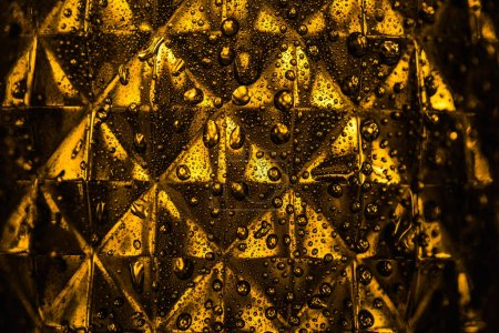 Photo for Close up view of geometric faceted glass with yellow illumination in dark - Royalty Free Image
