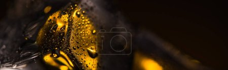 Photo for Close up view of wet square ice cube with yellow illumination, panoramic shot - Royalty Free Image