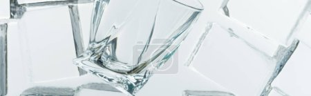 top view of transparent clear square ice cubes and empty glass on mirror, panoramic shot
