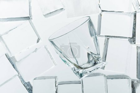 top view of transparent clear square ice cubes and empty glass on mirror