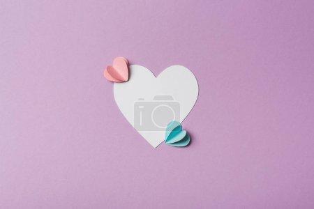 Photo pour Vue du dessus de la carte blanche avec des coeurs en papier coloré sur fond violet - image libre de droit