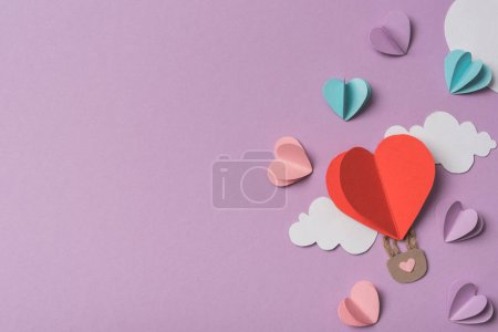Photo for Top view of colorful paper hearts and clouds around heart shaped paper air balloon on violet background - Royalty Free Image