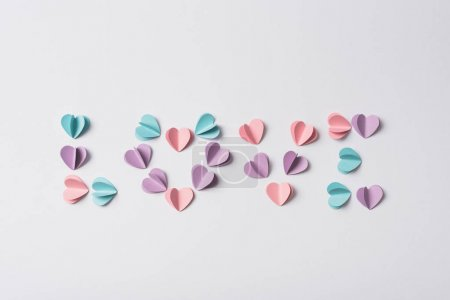 Photo pour Top view of love lettering made of colorful paper hearts on white background - image libre de droit