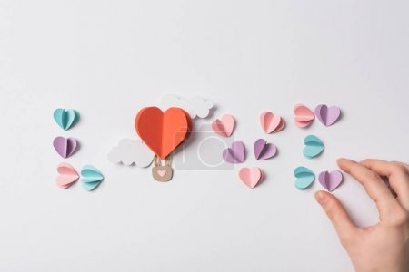 Photo pour Top view of love lettering made of colorful paper hearts and air bulloon with clouds on white background - image libre de droit