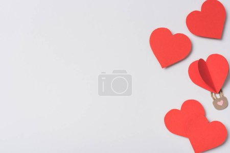 top view of red hearts and padlock on white background
