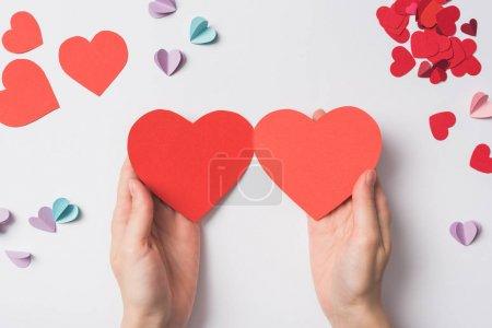 Photo pour Vue partielle d'une femme tenant des coeurs blancs en forme de cœur rouge sur fond blanc - image libre de droit