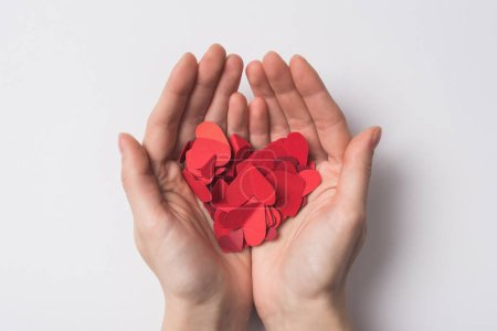 Photo for Partial view of woman holding paper red hearts on white background - Royalty Free Image