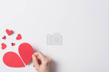 Photo for Cropped view of woman holding red broken heart pieces on white background - Royalty Free Image
