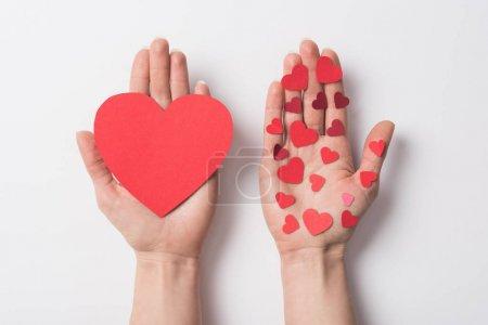 Photo pour Vue recadrée de la femme tenant des cœurs rouges sur fond blanc - image libre de droit