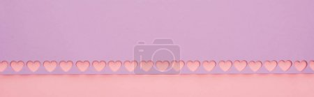 Photo for Top view of violet paper with cut out hearts on pink background, panoramic shot - Royalty Free Image