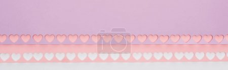 Photo for Top view of pink, violet paper with cut out hearts on white background, panoramic shot - Royalty Free Image