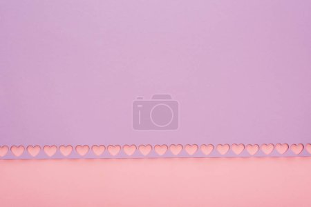 Photo for Top view of violet paper with cut out hearts on pink background - Royalty Free Image